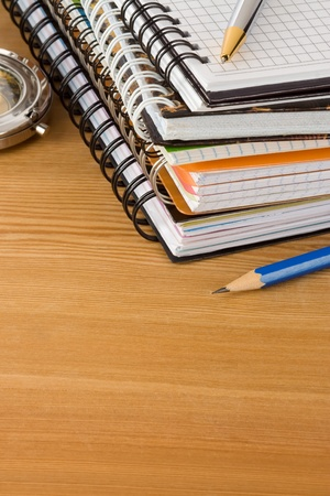 notebook and pens on wood background texture photo