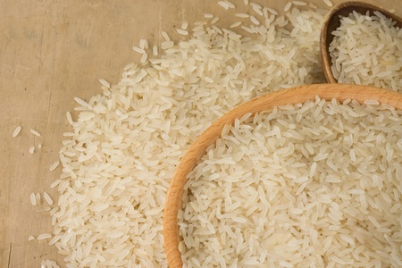 uncooked rice and wood spoon as background photo