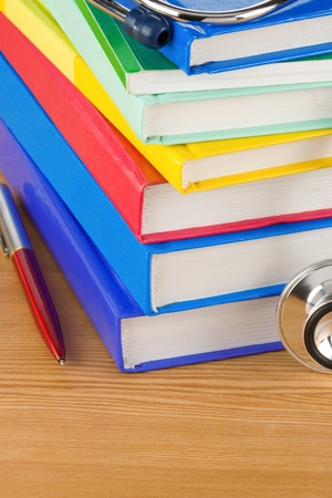 medical stethoscope with pile of book over wood  background photo