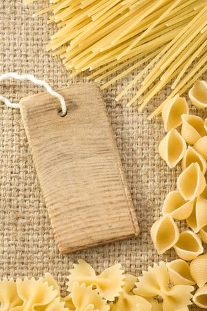 pasta and price tag on sack burlap as background photo