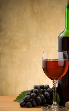 wine in glass and bottle with grape fruit on wood background