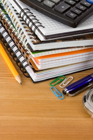 pile of notebook and pens on wood background texture photo