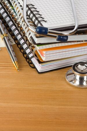 medical stethoscope with notebook on wood  background photo