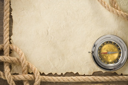 ropes and compass at old vintage ancient paper background texture photo