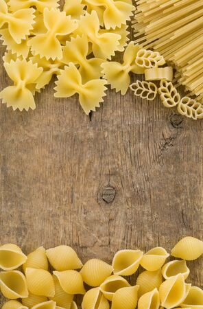 raw pasta on wood background texture photo