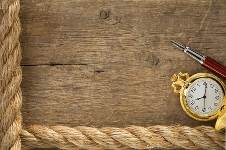 ship ropes and watch with ink pen on old wooden background photo