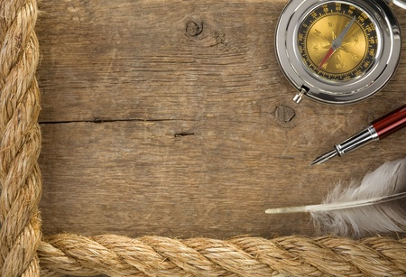 ship ropes and compass at old wooden background Stock Photo - 12311315