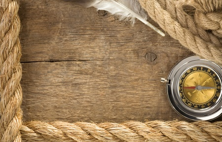 ship ropes and compass with feather at old wooden background photo