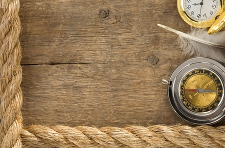 ship ropes and compass with feather at old wooden background Stock Photo - 12311318