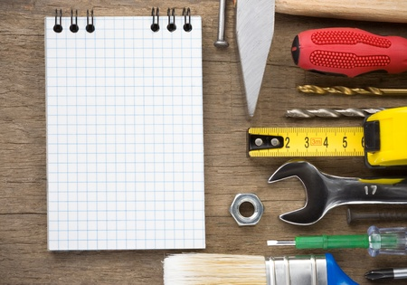 tools and notebook on wood texture background photo
