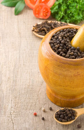 pepper in mortar with pestle and spices  ingredient on wooden texture photo