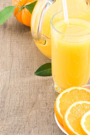 orange juice in glass and slices on wood background photo