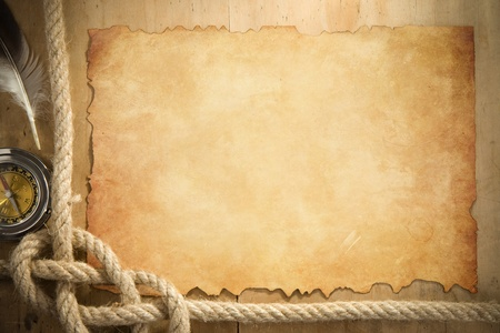 ship ropes and compass at parchment old paper background