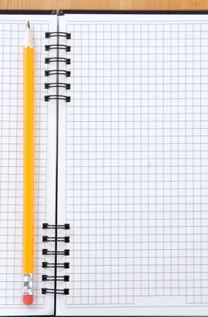 pencil on checked notebook at wood background Stock Photo - 12411181
