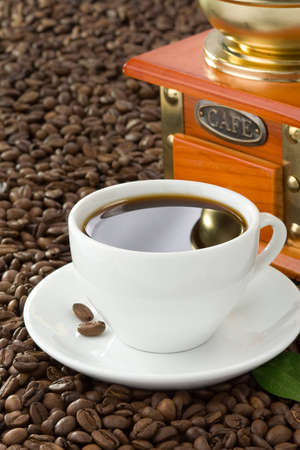 cup of coffee with beans and grinder photo