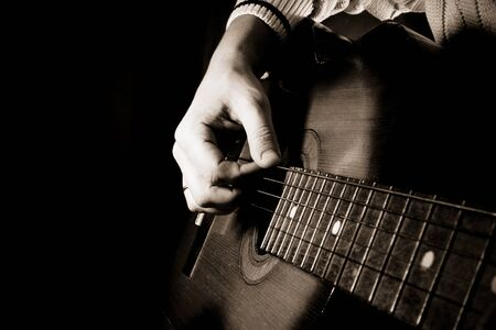 guy playing guitar: man playing guitar at black background Stock Photo