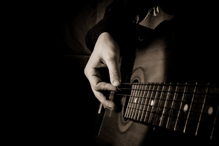 recordings: man playing guitar at black background Stock Photo