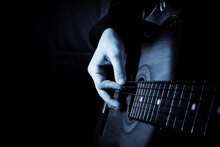playing music: blue guitar at black background