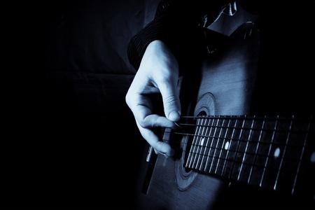 guy playing guitar: blue guitar at black background