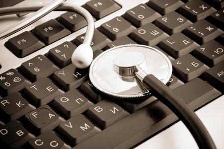 sepia stethoscope at keyboard background photo