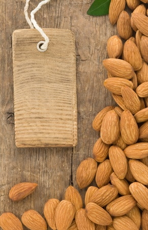 nuts almond fruit and tag label on wood background texture