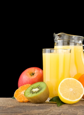 fresh tropical fruits and juice in glass isolated on black background photo