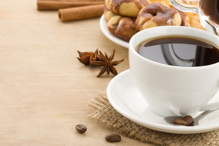 cup of coffee with beans and cakes on wood background photo