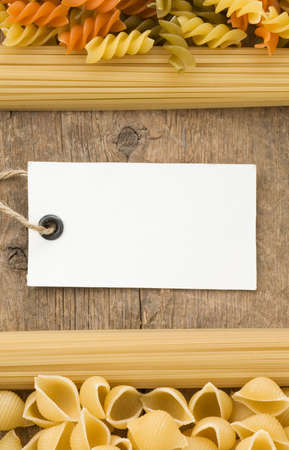 raw pasta and price tag on wood background texture photo