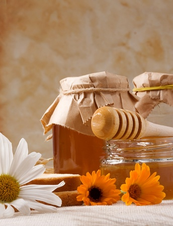 several flowers and honey on sackcloth photo