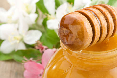 honey in glass and stick with blossom on wood background photo