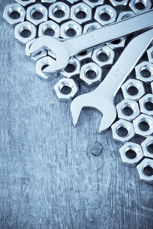 metal nuts and wrench tool on wood background texture photo