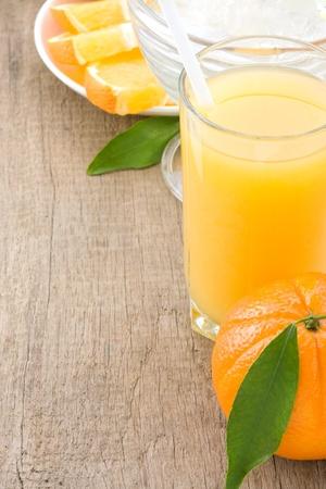 orange juice and glass on wood background photo