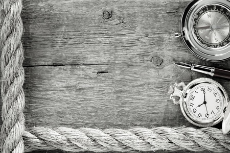 slipped: ship ropes and compass with pen on old vintage wooden background Stock Photo