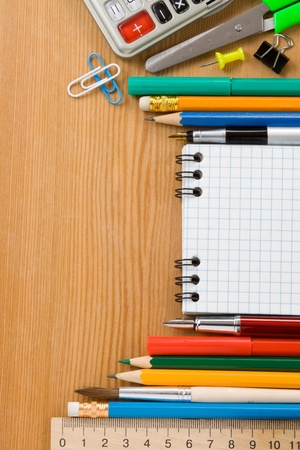 office supply: school supplies and checked notebook on wood background