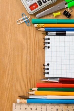 convivencia escolar: �tiles escolares y computadoras port�tiles comprobar en la madera de fondo