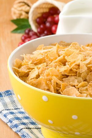 Bowl of corn flakes with berry and milk on wood photo