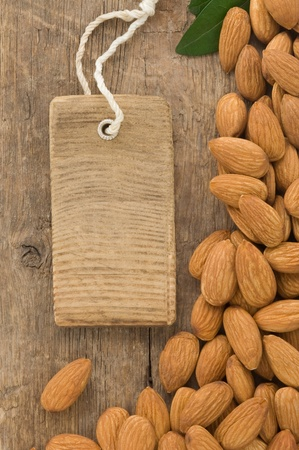 nuts almond and tag price on wood background photo