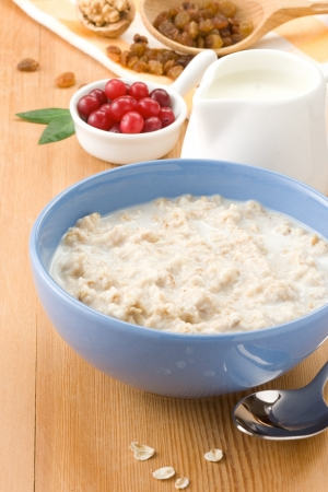 oatmeal bowl: Bowl of oatmeal with berry and milk on wood Stock Photo