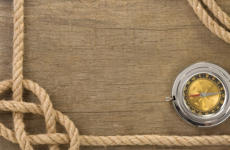 ship ropes and compass with pen on old vintage wooden background photo