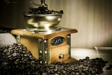 coffee grinder, beans and sacking on wood in night photo