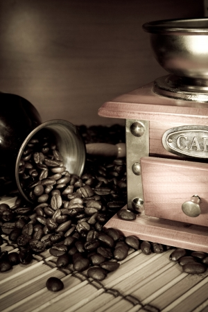 coffee beans, pot and grinder on sacking in sepia photo