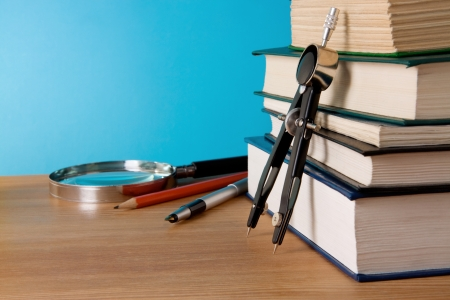 pen, pencil, pile of books and magnifier on wood table photo