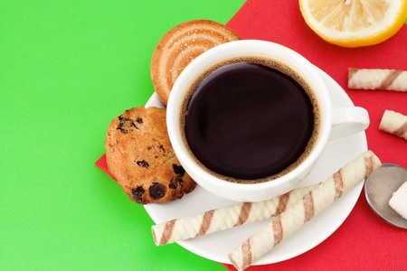 cup of coffee and cookies on green background photo