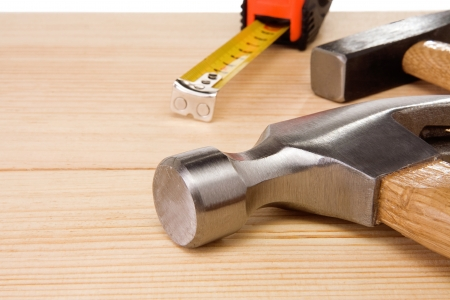 hammer and tape measure on wood brick photo
