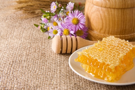 honeycomb, flowers and honey in pot on sacking