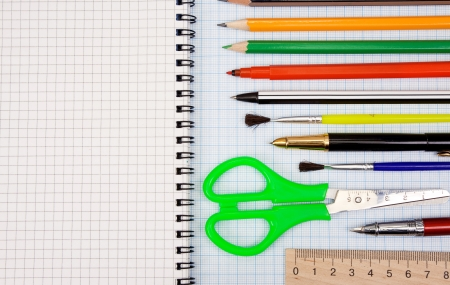 pens, pencils, paint brush and scissors on graph grid paper Stock Photo - 13779265