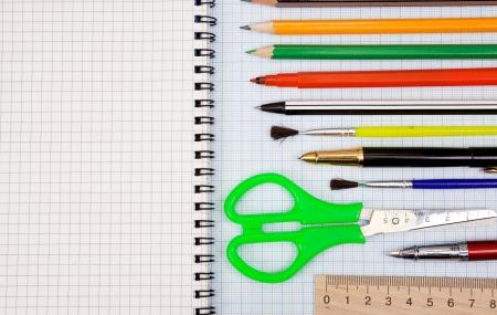 pens, pencils, paint brush and scissors on graph grid paper Stock Photo - 13779265