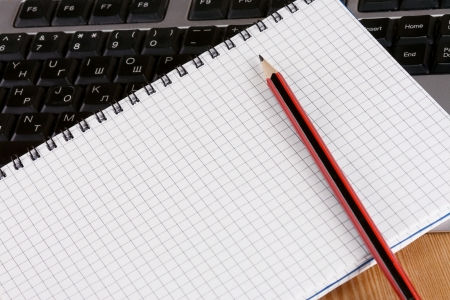 pencil and notebook on computer keyboard photo
