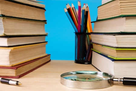 pile of books, magnifier and holder basket with pencils on blue background photo