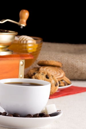 coffee beans, cup and grinder on sacking with cookies photo